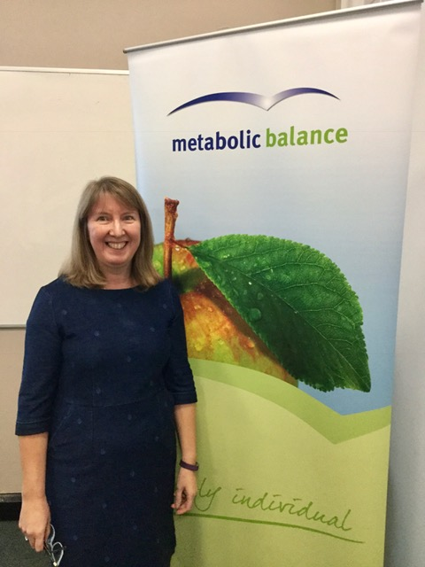 Metabolic Balance® Shirley Briars standing in front of a banner